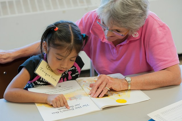 Mary Zeller, a member of Guardian Angels Parish in Kansas City, Mo., helps Jacqueline Gutierrez, 6, with reading at The Learning Club. The Learning Club offers students in the poorest part of the city tutoring and a consistent support system.