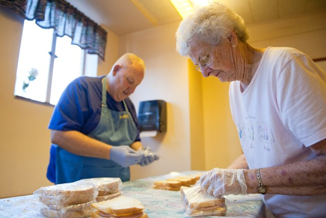 Larry Lesser, a member of Sacred Heart Parish in Topeka, and Mary Kirk, a member of Mater Dei Parish in Topeka, prepare the day's sandwiches. The ministry typically hands out more than 100 sandwiches a day.