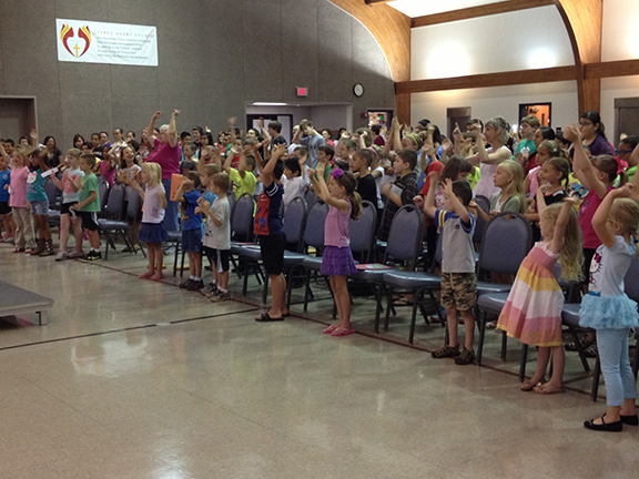 Students at Sacred Heart Church in Emporia begin a day of intensive summer religious education with a song about Noah and the ark. Rather than the traditional religious education paradigm — where students attend class each week — students at Sacred Heart attend a two-week session each summer.
