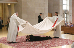 Photo by JD Benning Benedictine Father Marion Charboneau (left) and Prior James Albers cover Brother Leven with a funeral pall to symbolize his death to the world. Brother Leven emerges from beneath the pall, symbolically resurrecting to new life as a monk.