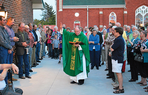 PHOTO COURTESY OF TODD SHEPPARD Father Pat Sullivan, pastor of St. Columbkille Parish in Blaine, blesses the parish's new church hall on Sept. 29. With the whole parish community pitching in, the church hall was completed in record time.