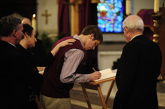 Joe Levinson, 18, a member of Holy Angels Parish in Basehor, signs the Book of the Elect at the Rite of Election on Feb. 24 at the Cathedral of St. Peter in Kansas City, Kan. Photo by Elaina Cochran.