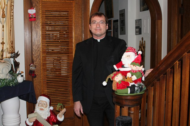 Father Tim Haberkorn stands ready to greet all comers in the main hallway of the rectory at Sacred Heart-St. Joseph Parish in Topeka, where he will hold his annual open house Dec. 14. Although the rectory will be decked out for the season in his personal collection of Christmas memorabilia, he has an extensive relic collection as well.