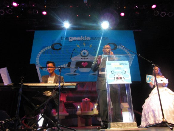 Olivia is on the far right with the cards identifying the sponsors during the musical number at The Geekie Awards.