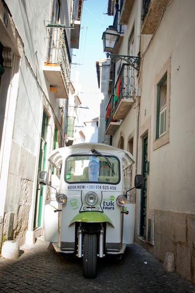 A Tuk Tuk squeezes through historic Lisbon