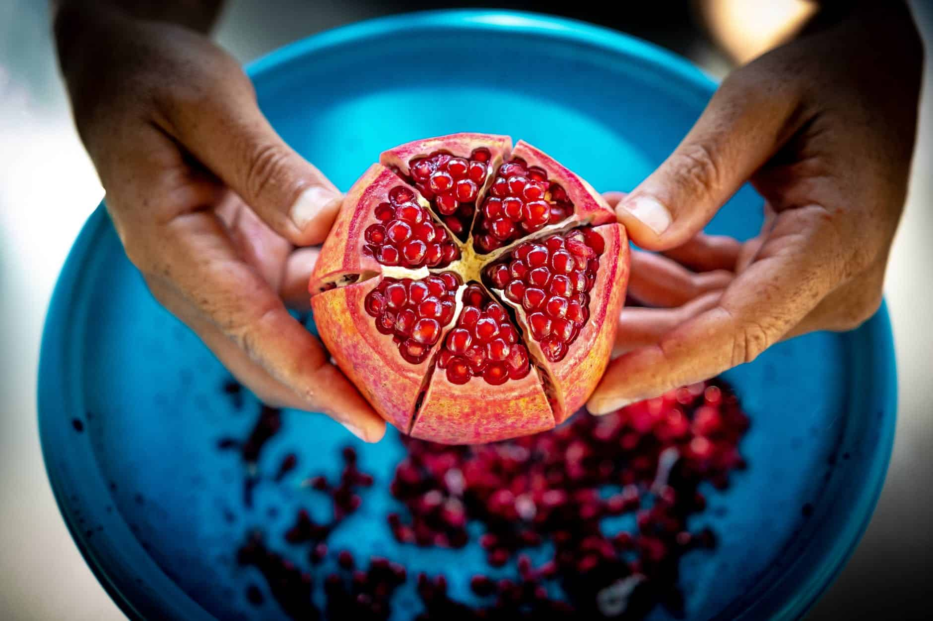 close up photo of person holding pomegranate fruit