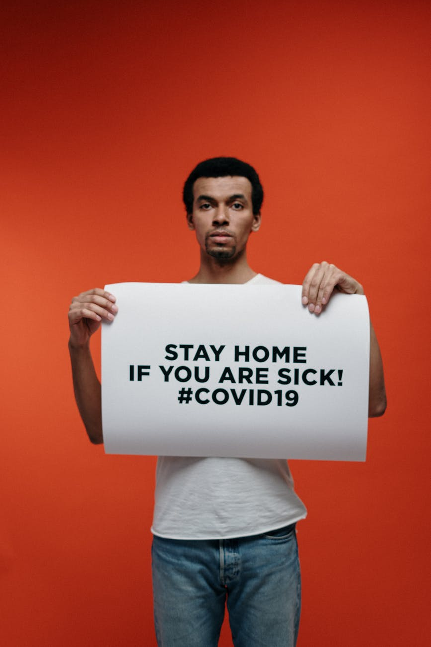 man in white crew neck t shirt holding stay at home sign