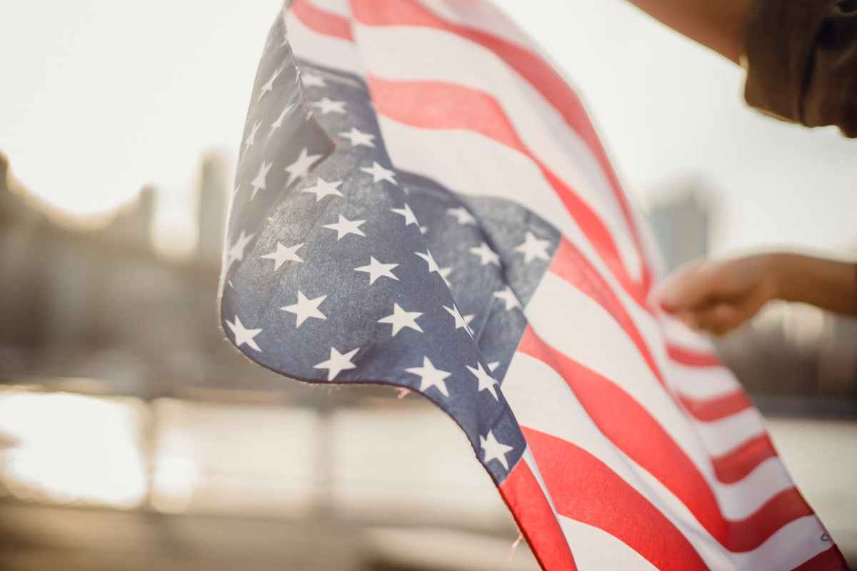 crop person holding american flag in wind