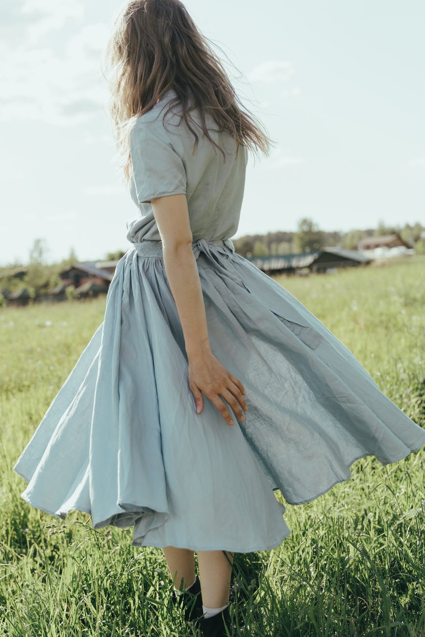 woman in white and blue dress standing on green grass field