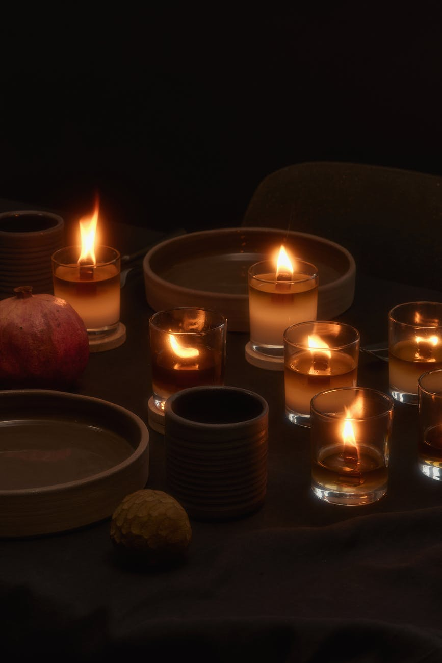 burning candles placed near ceramic plates and grapefruit