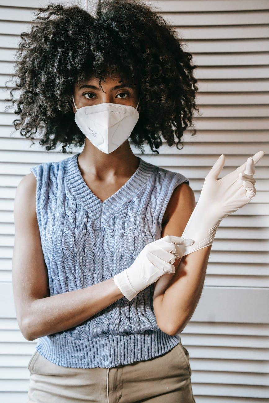 ethnic woman putting on gloves during coronavirus pandemic