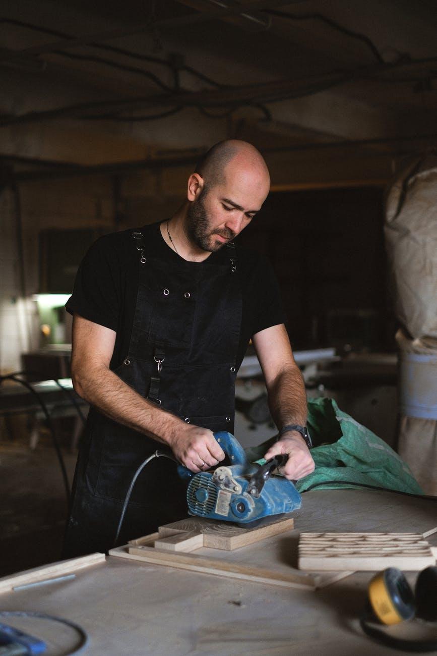 focused artisan working with belt sander