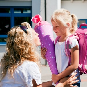 A blond woman kneels talking to her daughter who is holding a purple sleeping bag and wearing a pink backpack.