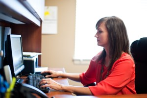 A woman in a red shirt sitting at a computer working with hands on keyboard and mouse.