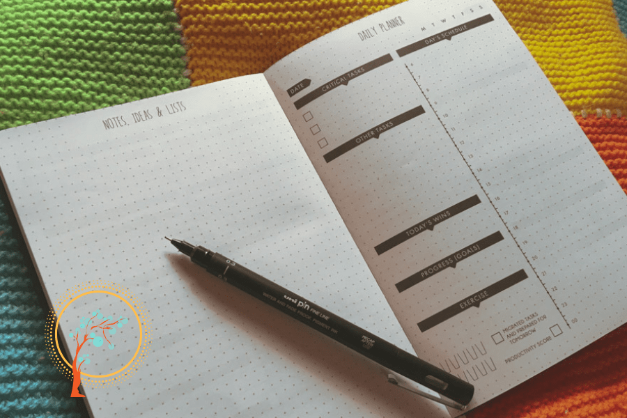 Image of open planner and pen with the life spotters logo