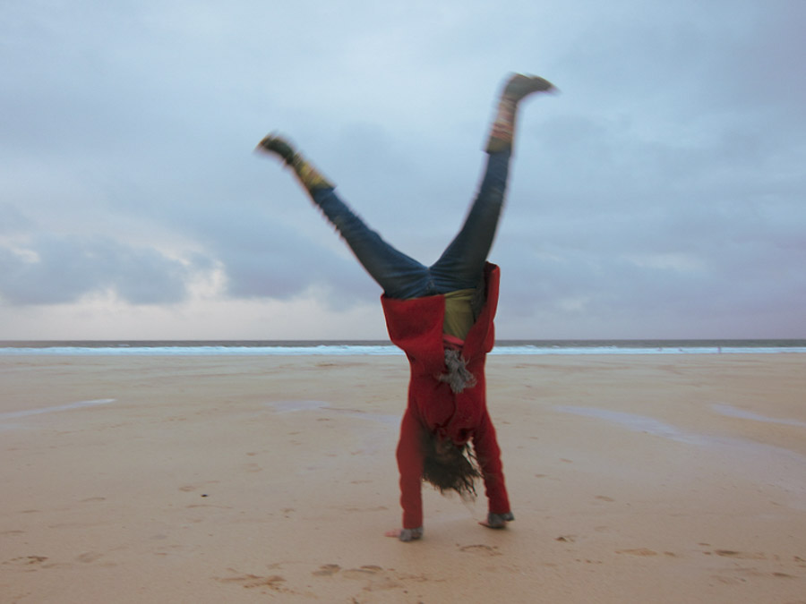 image of a woman doing cartwheels on the beach