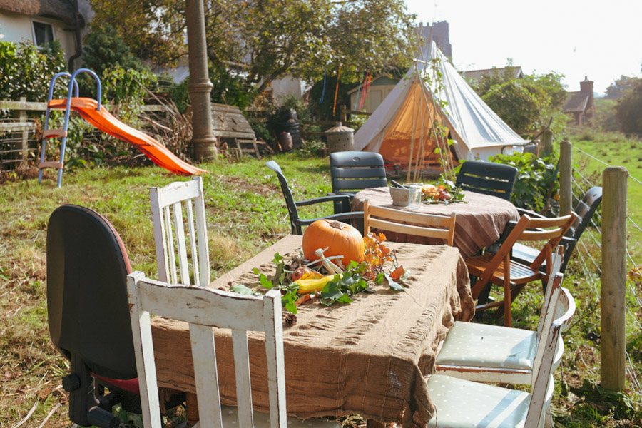image of tables and mismatched chairs set out in a garden and decorated with squashes and autumnal leaves