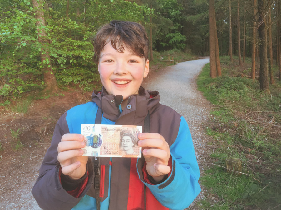 image of a smiliing boy standing in the woods holding a 10 pound note