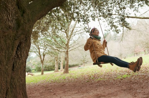 Image of a woman swinging forwards on a rope swing hung from a tree