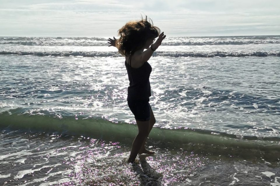 image of a woman dancing in the waves at the seas edge