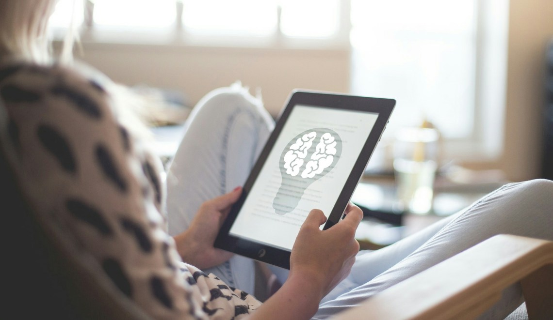image of a woman reclining holding a tablet with a diagram of a brain
