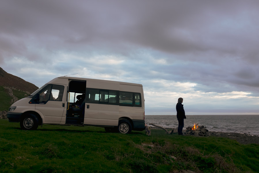 image of a campervan parked by the beach and a man standing by a campfire