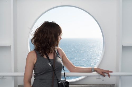 image of the author looking out of a porthole window to sea, looking contemplative