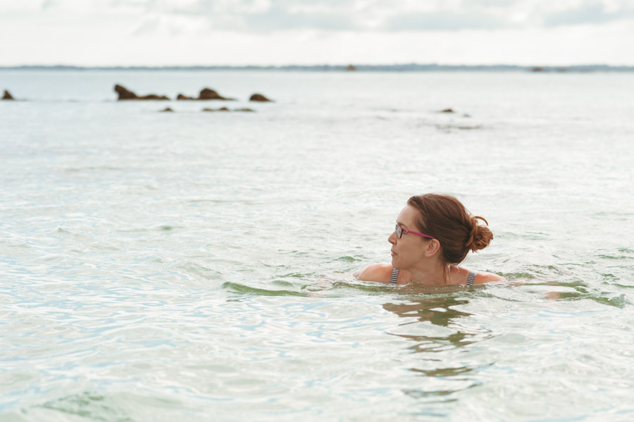 Image of a woman swimming in the sea in the early morning light