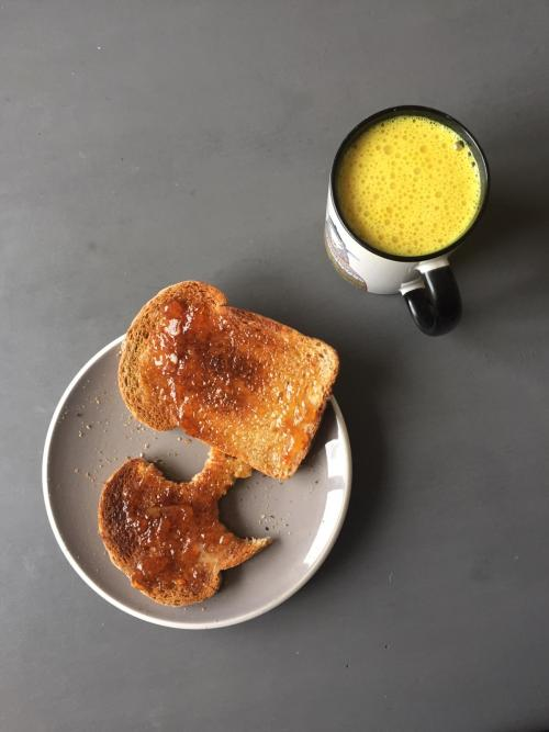 image of a mug of turmeric milk alongside 2 slices of toast
