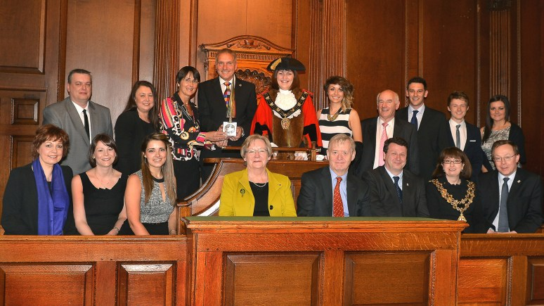 Lincoln Mayor Councillor Karen Lee presents the Lincoln Civic Award to Running Imp International's directors (third and fourth from left) Caroline Birkin and Chris Illsley, surrounded by other members of the Lincoln Civic party, Running Imp staff, and representatatives of the Lincoln Civic Award trustees and former winner The Rotary Club of Lincoln Colonia.