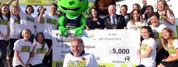 Running Imp founder Chris Illsley presented St Barnabas with a £5 and the 2013 mile celebration, front centre. Pictured: teams from Running Imp, St Barnabas Lincolnshire Hospice and Mayor of Lincoln councillor Patrick Vaughan . Photo: Steve Smailes for The Lincolnite