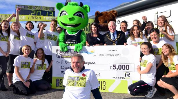 Running Imp founder Chris Illsley presented St Barnabas with a £5k donation at the 2013 mile celebration (Chris pictured front centre). Pictured: teams from Running Imp, St Barnabas Lincolnshire Hospice and Mayor of Lincoln councillor Patrick Vaughan . Photo: Steve Smailes for The Lincolnite