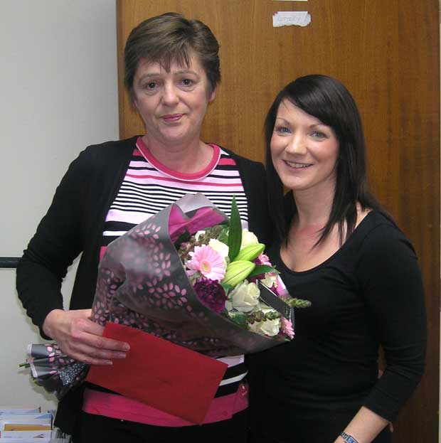 Marie Pattison receives a bunch of flowers and spa day gift voucher from Fundraising Manager Veronica Brien. Photo: St Barnabas
