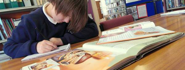 A child doing homework in a library in Lincolnshire