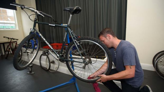 James Irvine repairing a bike. Photo: Steve Smailes for The Lincolnite