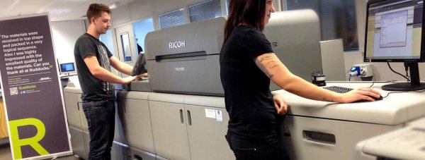 Isobel Scarlett and Adam Bratley, the two newest additions to the digital production team, working on the new Ricoh C9100 printing press.
