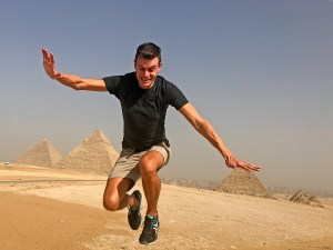 John Line jumping in front of the Pyramids of Giza, Cairo, Egypt.