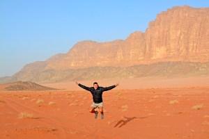 John Line jumping in the Wadi Rum Desert, Jordan.