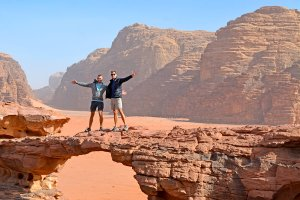 Scott Swiontek and John Line on a natural rock bridge in the Wadi Rum Desert, Jordan.