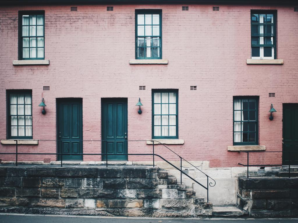 Traditional real estate financing for vacant properties with no cash flow. This vacant apartment building is pink brick with deep teal doors and window frames.