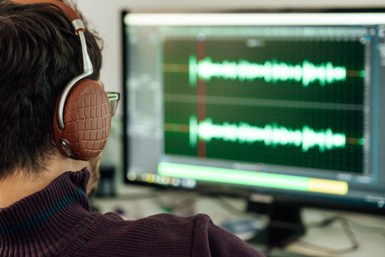 The man in the photo studio records and modifies singing, voice and music for commercial use. Works in an audio editor in a computer with headphone