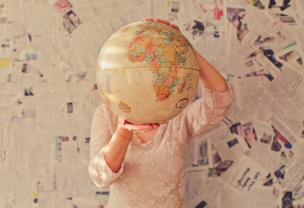 girl holding globe - how I afforded travel in my early twenties