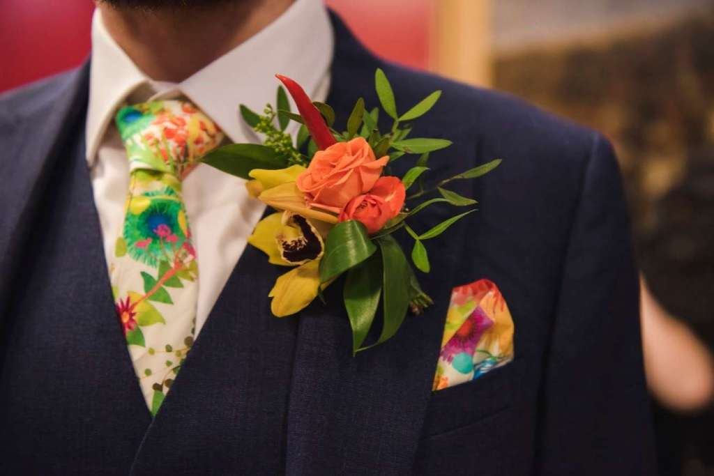 Groom wearing brightly coloured button hole, tie and pocket square