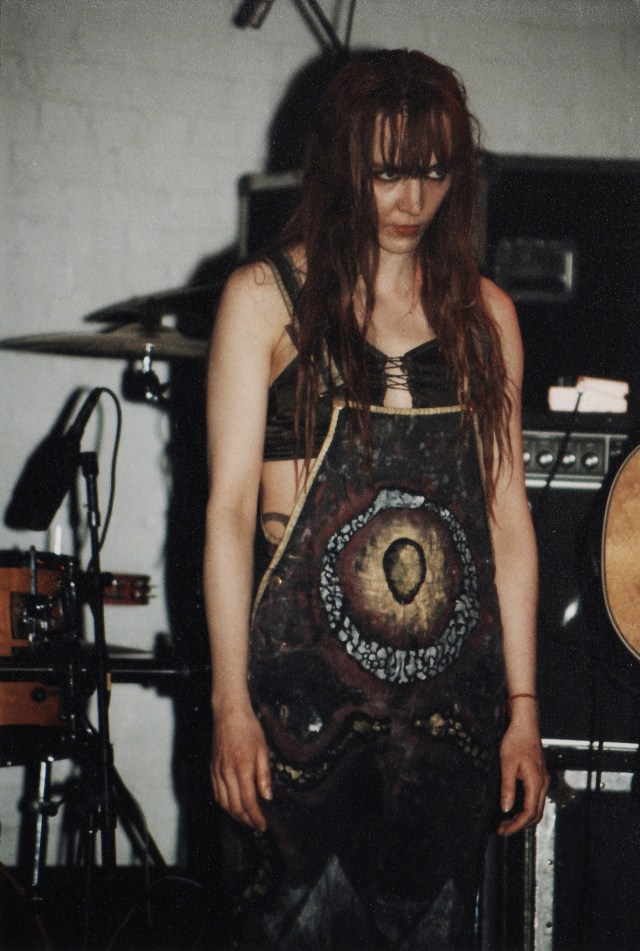 on stage in Swans wearing hand-painted overalls by artist Joshua Seaver