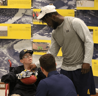 Larry Prout Jr. talks with two of his friends on the Michigan football team, De'Veon Smith (right) and John O'Korn Ikneeling). (Photo by Tim R obinson