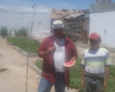 Francisco and his 12-year-old son Bernardo enjoying the first watermelon from the community garden at Las Alitas