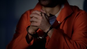 Imprisoned male in handcuffs holding cross and praying