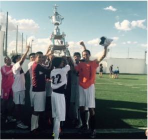 Boys soccer team holding up trophy.