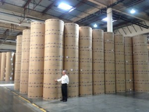 Darrell stands next to massive rolls of newsprint. Each weighs about 1500 pounds (photo by Nikki Kreuzer)