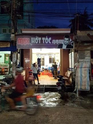 A motorbike speeds by a local hair salon in An Thoi.